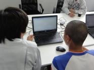 パソコンに向かって、社員の説明を受けている中学生の写真