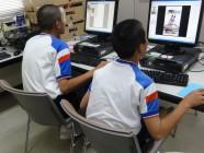 パソコンに向かってポスター制作を体験している二人の中学生の写真