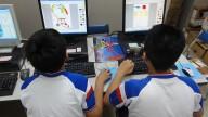 パソコンに向かって、2人の中学生が一生懸命ポスターを制作している写真