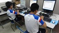パソコンの前で資料製作を体験している2人の中学生の写真