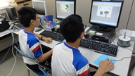 CDケースの背表紙をパソコンで制作している二人の中学生の写真